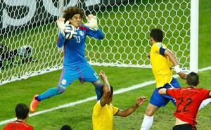 4.+Mexico's+Guillermo+Ochoa+(L)+deflects+the+ball+during+a+goal+attempt+by+Brazil's+Thiago+Silva+(top+R)+dur
